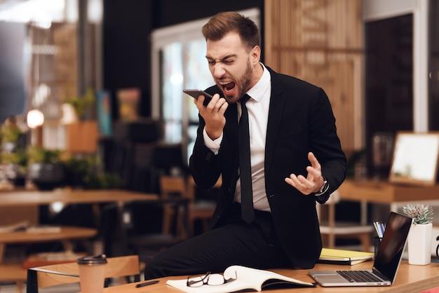 Een man in een pak praten luid aan de telefoon.