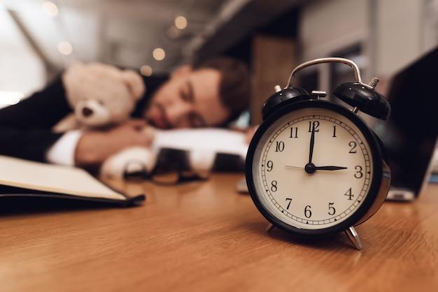 Een man in een pak slaapt op de werkplek.