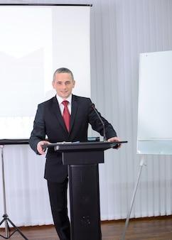 Een man in een pak staat achter het podium en zegt.