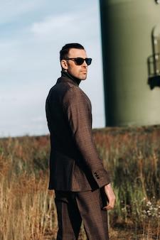 Een man in een pak staat naast een windmolen tegen een veld en een blauwe lucht. zakenman in de buurt van de windmolens.