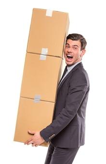 Een man in een pak tilde vele dozen boven zichzelf uit.