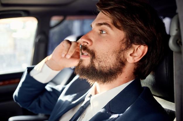 Een man in een pak zit in de auto en praat aan de telefoon