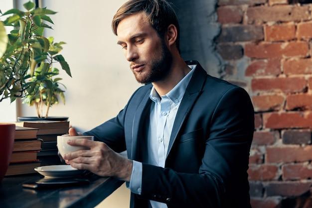 Een man in een pak zit in een café met een kopje koffie vrijetijdsprofessional