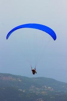 Een man in een parachute vliegt over de bergen