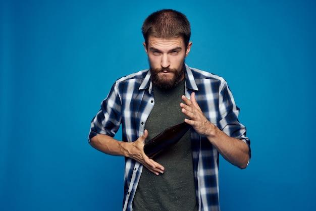 Een man in een plaid shirt drinken bier alcohol emotie geïsoleerde achtergrond
