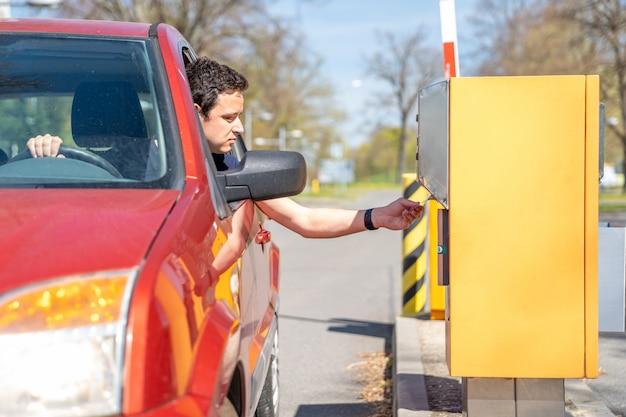 Een man in een rode auto krijgt een kaartje in een parkeermeter