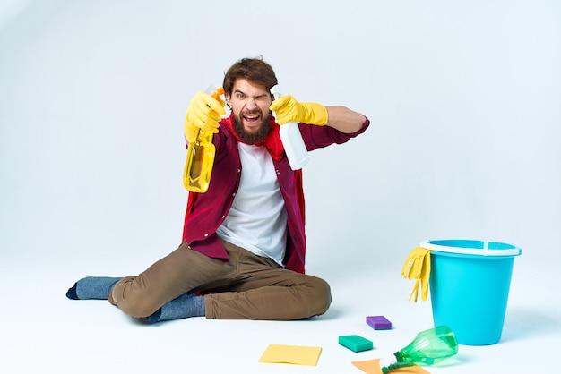 Een man in een rode regenjas die thuis de vloeren wast en diensten verleent.
