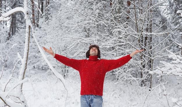 Een man in een rode trui staat in een besneeuwd bos met zijn handen in de lucht. familie wintervakantie.