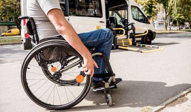 Een man in een rolstoel gaat naar de lift van een gespecialiseerd voertuig