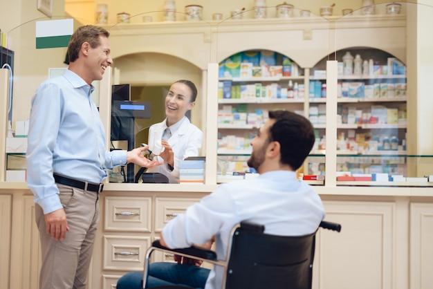 Een man in een rolstoel is in een apotheek.