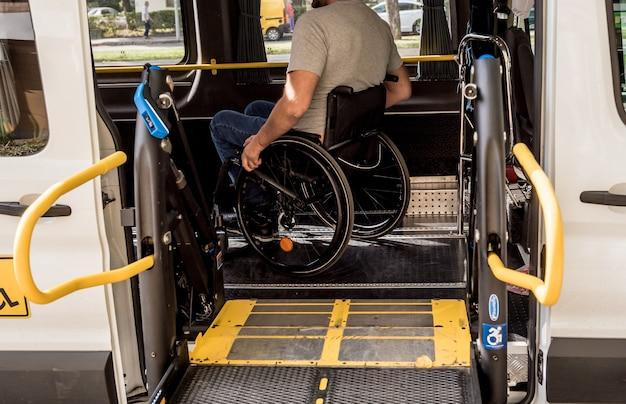Een man in een rolstoel op een lift van een voertuig voor mensen met een handicap.