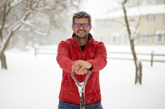 Een man in een rood jasje glimlacht en houdt een sneeuwschop vast