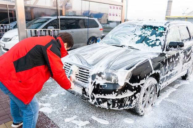 Een man in een rood jasje veegt een met schuim bedekte zwarte auto af met een borstel bij een autowasstraat. vooraanzicht