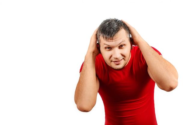 Een man in een rood t-shirt bedekt zijn hoofd met zijn handen en verbergt zich voor iets dat valt.