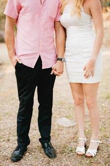 Een man in een roze overhemd en een vrouw in een korte witte jurk staan naast elkaar en houden teder een hand vast