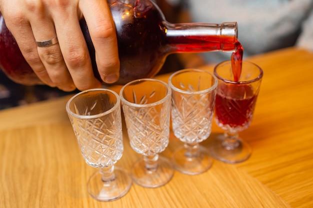 Een man in een rustiek uitziend shirt giet whisky in glazen whisky drinkt een alcoholische drank