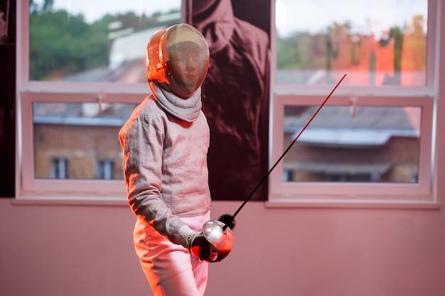 Een man in een schermpak met een zwaard in zijn hand, neonlicht. een jong model traint en traint in beweging, actie. sport, jeugd, gezonde levensstijl.