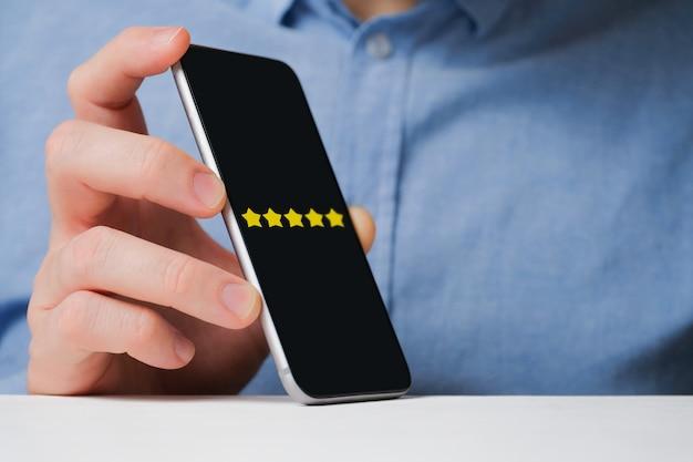 Een man in een shirt toont abstract een waardering van vijf sterren in een smartphone. beste score.