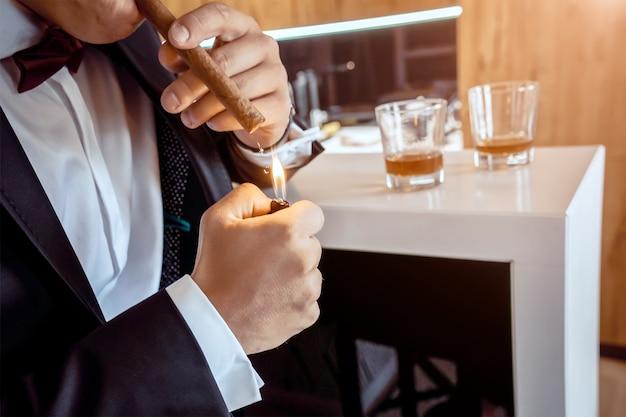 Een man in een smoking steekt een sigaar op