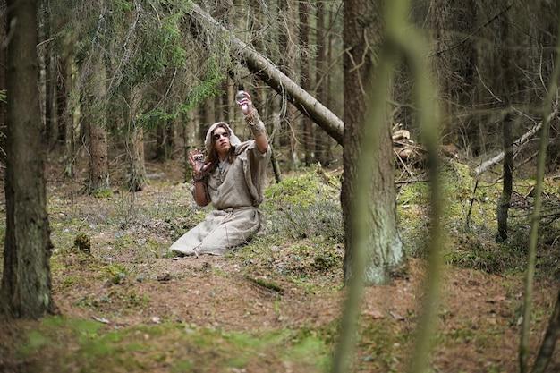 Een man in een soutane brengt een ritueel door in een donker bos met een kristallen bol en een boek