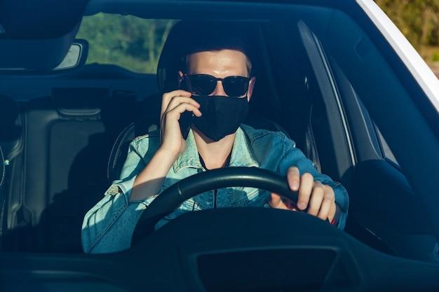 Een man in een spijkerjasje en een zwarte bril met een masker op zijn gezicht praat aan de telefoon tijdens het autorijden