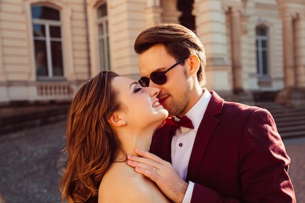 Een man in een stijlvolle bril raakt zijn bruid zachtjes aan
