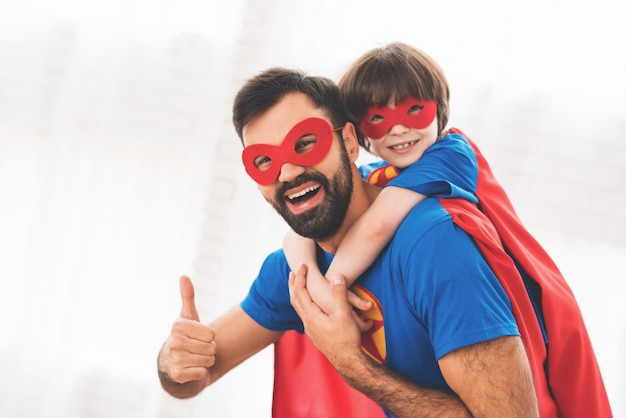 Een man in een superheld kostuum met een kind op zijn schouders.