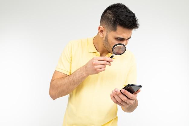 Een man in een t-shirt houdt een vergrootglas en een telefoon vast op een witte achtergrond met kopie ruimte.