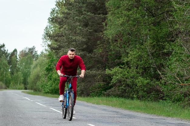 Een man in een trainingspak op een fiets rijdt op een weg in het bos. het concept van een gezonde levensstijl, cardiotraining. copyspace.