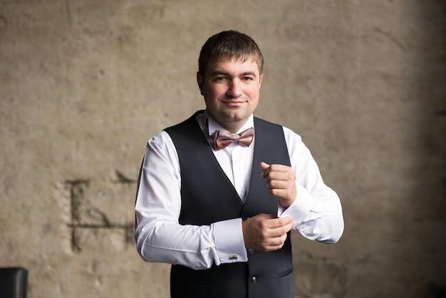 Een man in een vest maakt een manchetknoop vast aan zijn mouw