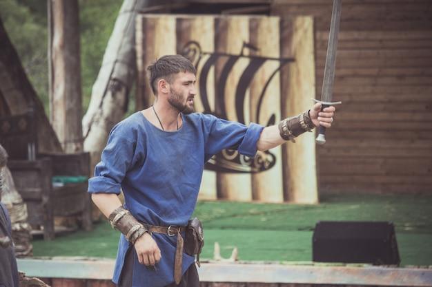 Een man in een viking-kostuum pakt een zwaard op