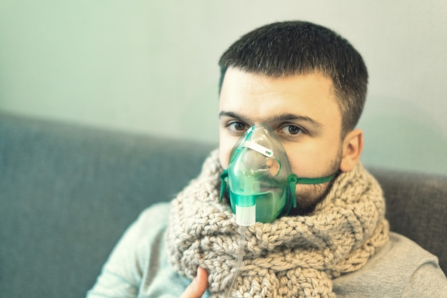 Een man in een warme sjaal en een groen inhaleermasker