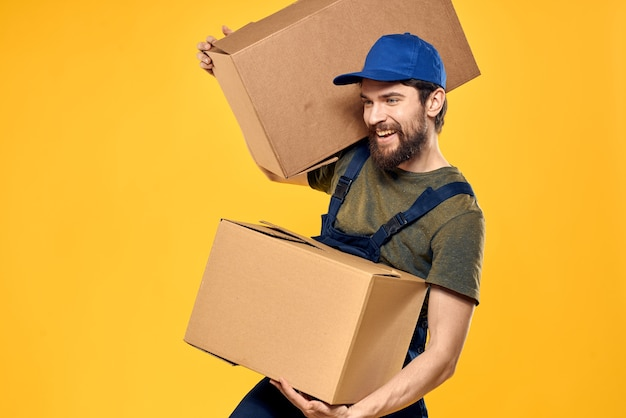 Een man in een werkend uniform met pakketten op een gele achtergrond.