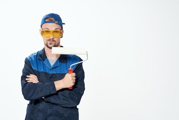 Een man in een werkuniform die de muren schildert en het huis repareert