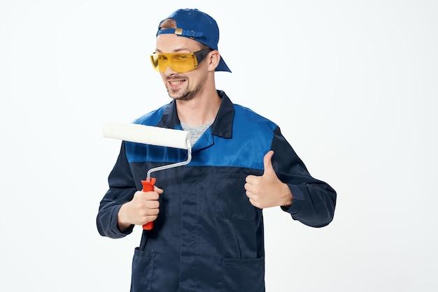 Een man in een werkuniform een roller voor het schilderen van muren in zijn handen decoratie reparatie