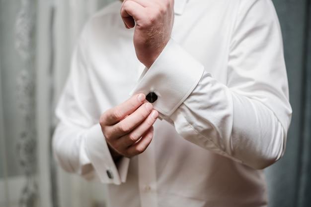 Een man in een wit overhemd de bruidegom knoopt de manchetknopen dicht de bruidegoms vergoedingen
