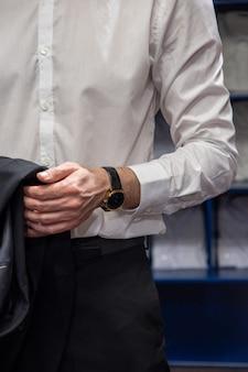 Een man in een wit overhemd, een zwarte broek, een zwart horloge, een jas aan zijn hand. concept van succesvolle zakenman