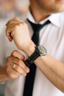 Een man in een wit overhemd en stropdas legt een horloge aan zijn hand tijdens de voorbereiding op de bruiloft