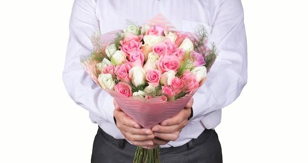 Een man in een wit overhemd heeft een groot boeket kleurrijke rozen in zijn handen als cadeau