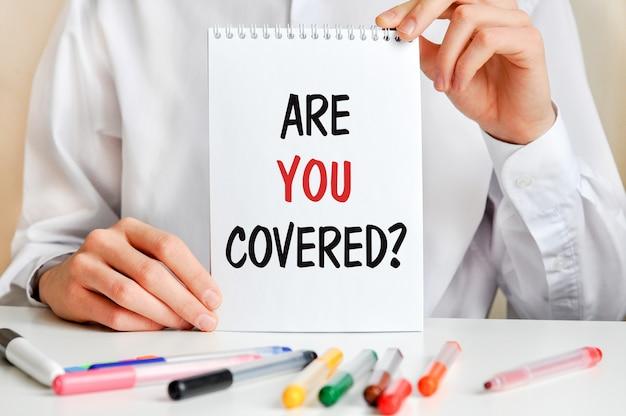 Een man in een wit overhemd houdt een vel papier vast met de tekst: are you covered