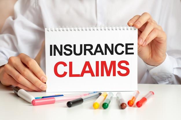 Een man in een wit overhemd houdt een vel papier vast met de tekst insurance claims