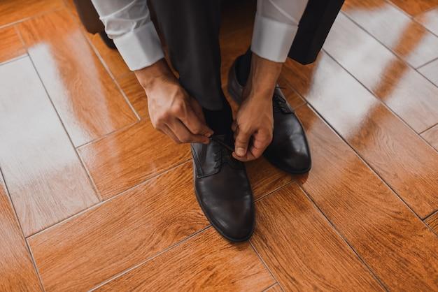 Een man in een wit overhemd in een klassieke donkere broek trekt de veters van zijn schoenen strak op een zwarte tegelvloer.