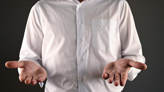 Een man in een wit overhemd maakt een hulpeloos gebaar.