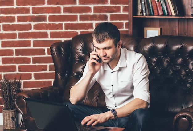 Een man in een wit overhemd praat aan de telefoon.