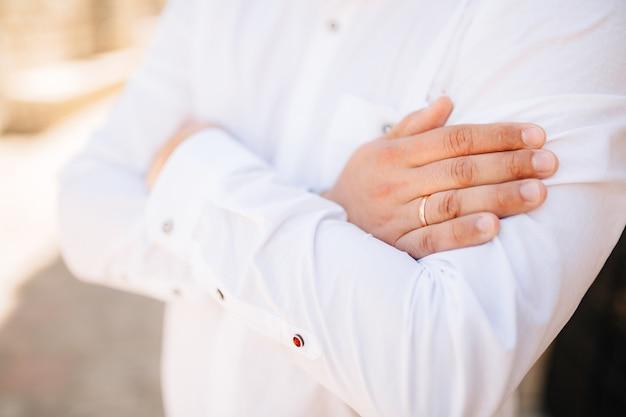 Een man in een wit overhemd sloeg zijn armen over zijn borst