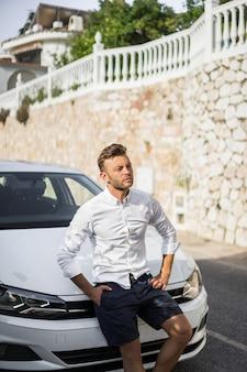 Een man in een wit overhemd zit op de motorkap van een auto.
