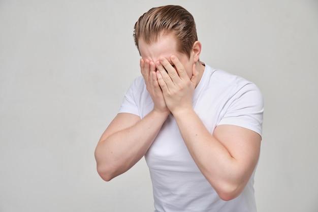 Een man in een wit shirt huilt over zijn gezicht met zijn handpalmen. het concept van diepe depressie.