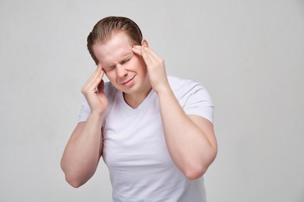 Een man in een wit shirt masseert zijn hoofd. het concept van hoofdpijn, migraine.