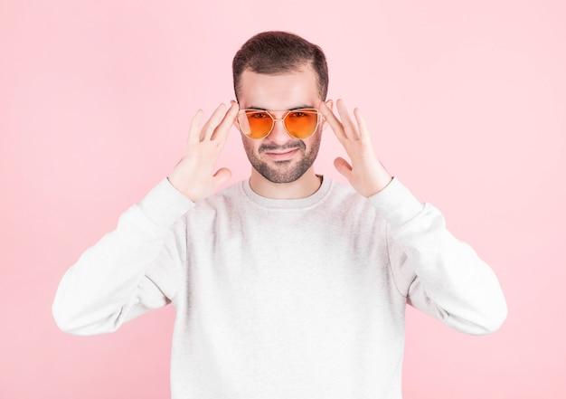 Een man in een wit sweatshirt zet een rode, heldere bril af met twee handen op een roze muur