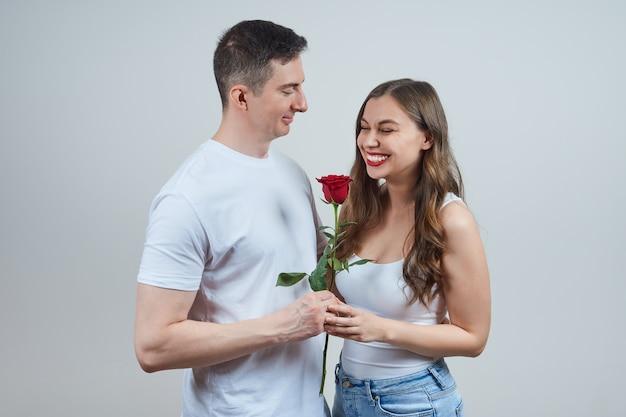 Een man in een wit t-shirt geeft een rode roos aan een zaaiende blondine